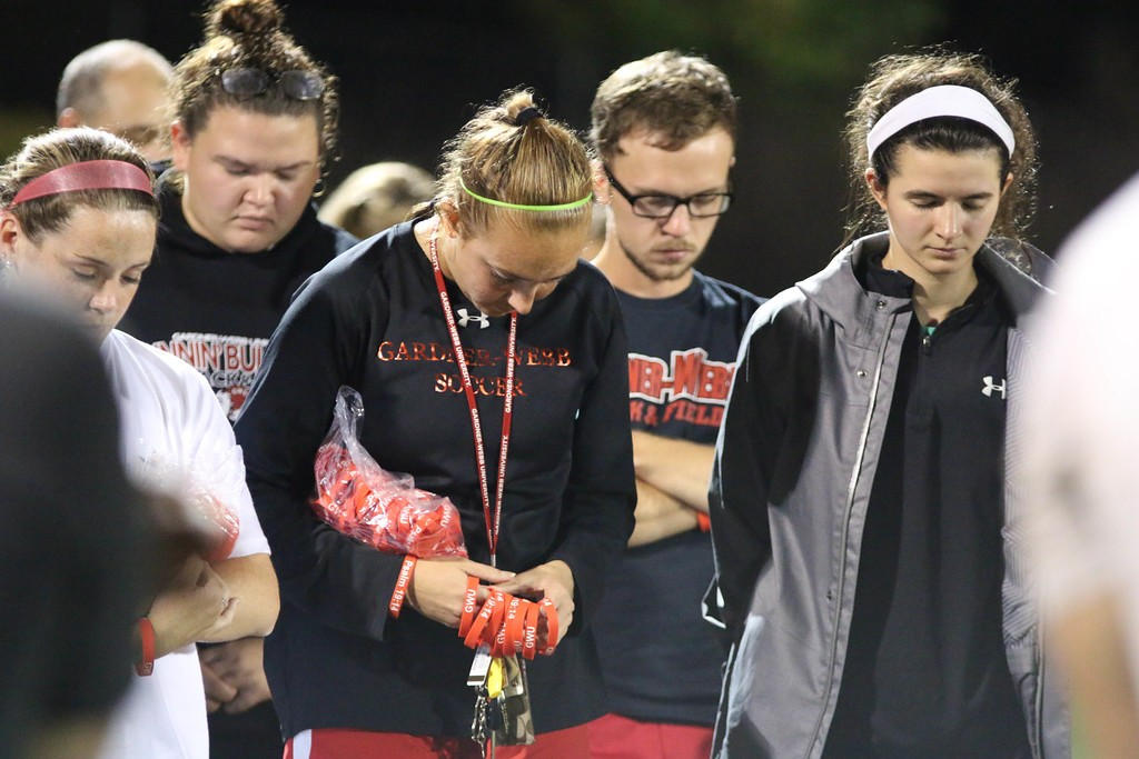 Students bow their heads in prayer over the team and all athletics after the game.