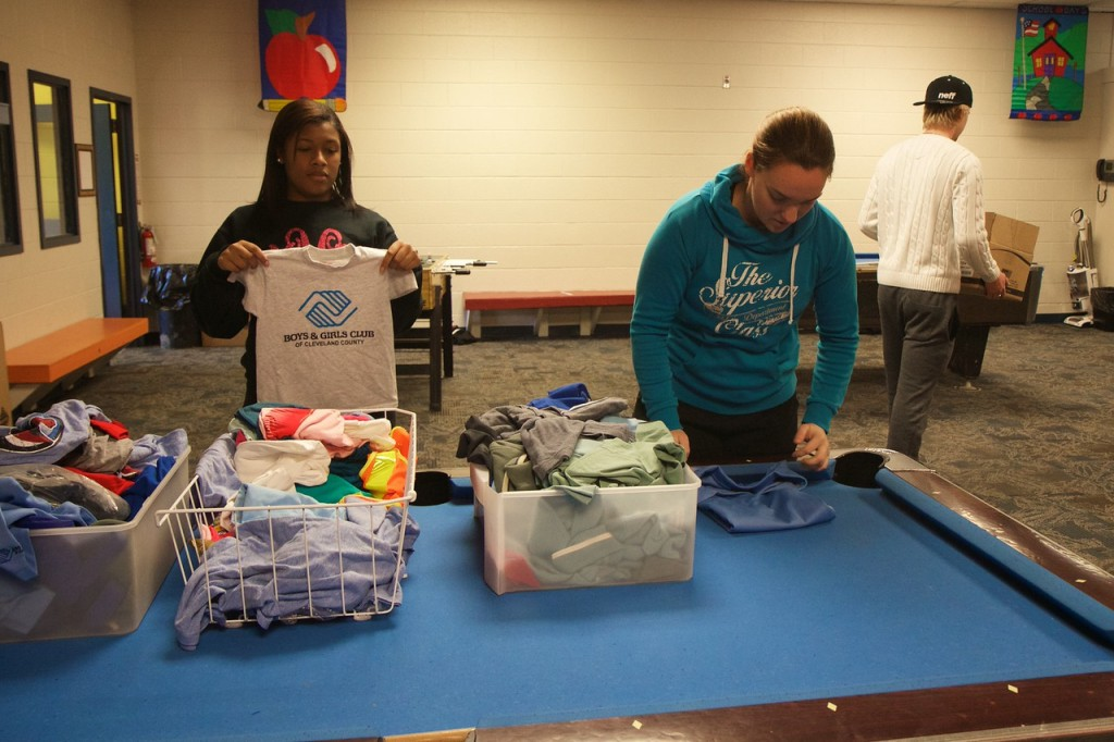 Two students fold clothes at the Boys and Girls Club.