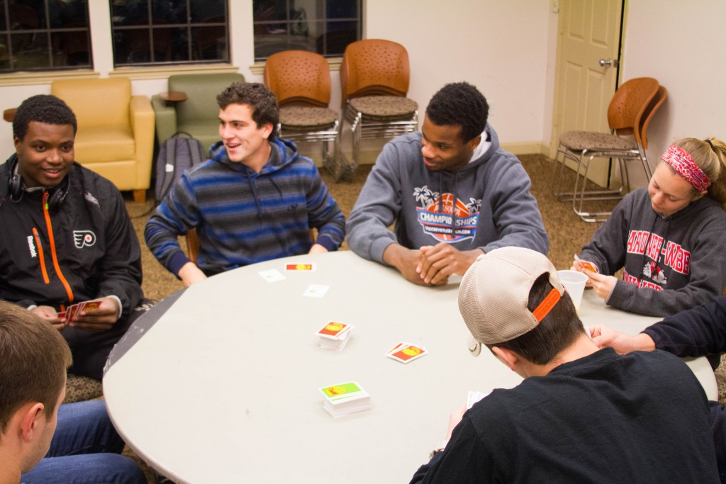 Students gather around a table to play Apples to Apples.