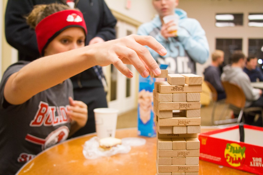 Another student stacks her Jenga block on the top of the stack carefully as to not knock over the stack.